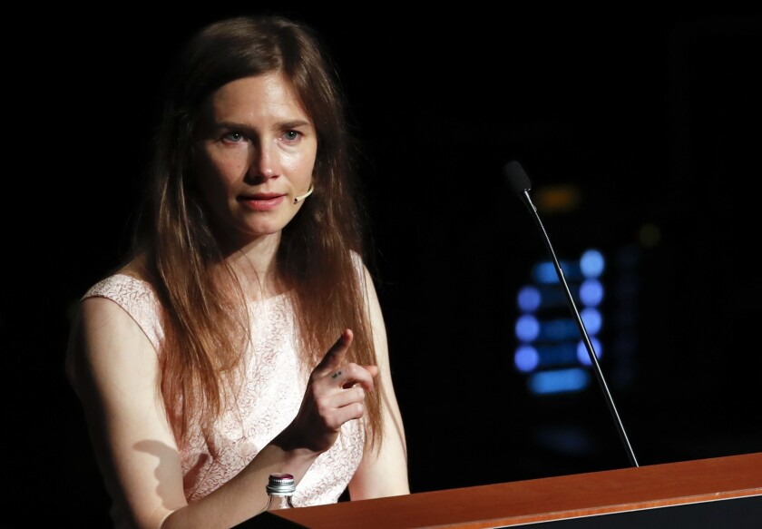 Amanda Knox points while speaking at a lectern