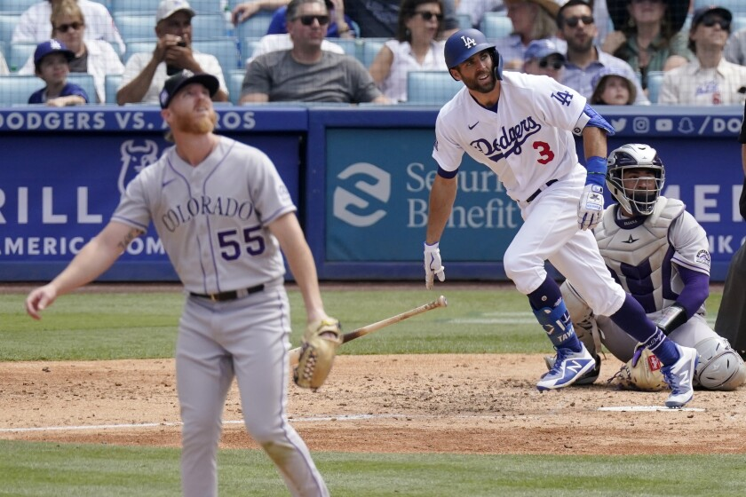 Los Angeles Dodgers' Chris Taylor, center, runs to first as he hits a solo home run while Colorado Rockies starting pitcher Jon Gray, left, watches along with catcher Elias Diaz during the fifth inning of a baseball game Sunday, July 25, 2021, in Los Angeles. (AP Photo/Mark J. Terrill)