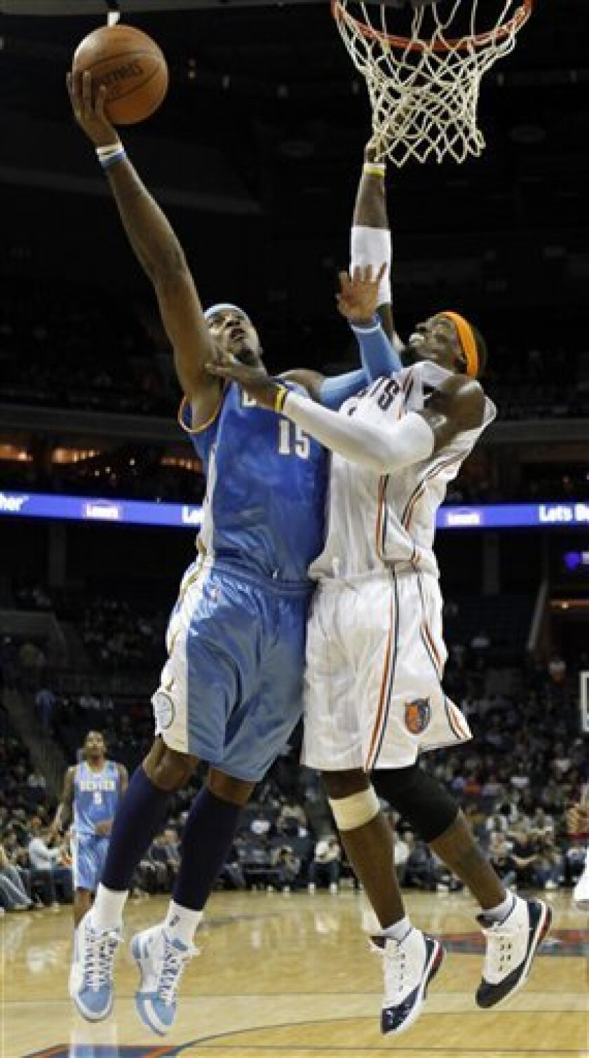 Denver Nuggets' Carmelo Anthony (15) shoots over Charlotte Bobcats' Gerald Wallace (3) in the first half of an NBA basketball game in Charlotte, N.C., Tuesday, Dec. 8, 2009. (AP Photo/Chuck Burton)