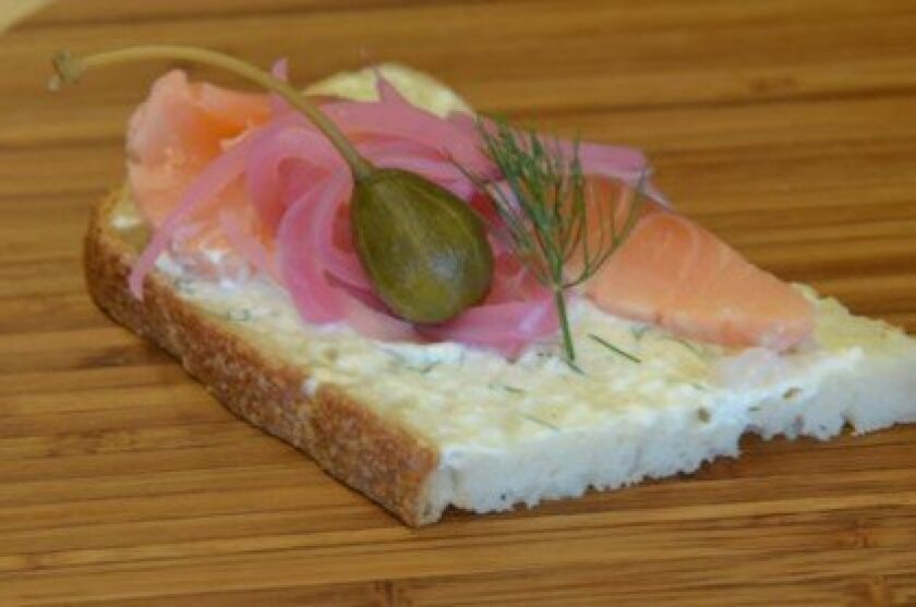Smoked Salmon on sourdough with dill cream cheese, caper berries and pickled onions.