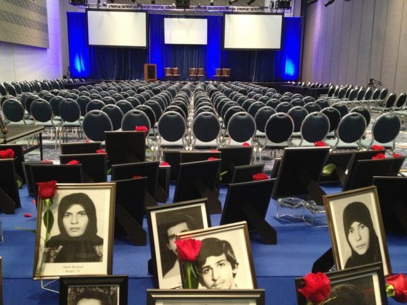 Pictures of Iranian political prisoners are arrayed on a table at the Anaheim Convention Center preceding a forum on U.S. policy toward Iran.