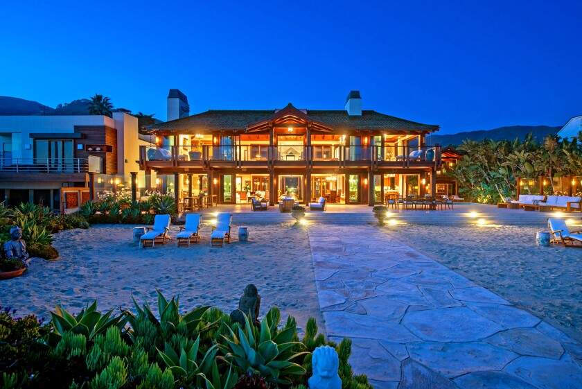 """""""James Bond"""" star Pierce Brosnan is shooting for nine figures in Malibu, where his Thai-inspired retreat on Broad Beach just hit the market for $100 million. The oceanfront retreat spans more than an acre with two homes that combine for five bedrooms and 14 bathrooms. Past a pair of carved teak gates, the verdant grounds are filled with palm trees, tropical flowers, travertine courtyards and wraparound lanais."""