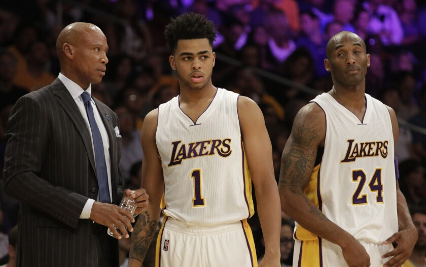 Lakers Coach Byron Scott chats with rookie guard D'Angelo Russell (1) as Kobe Bryant (24) listens during the first half of their game Sunday.