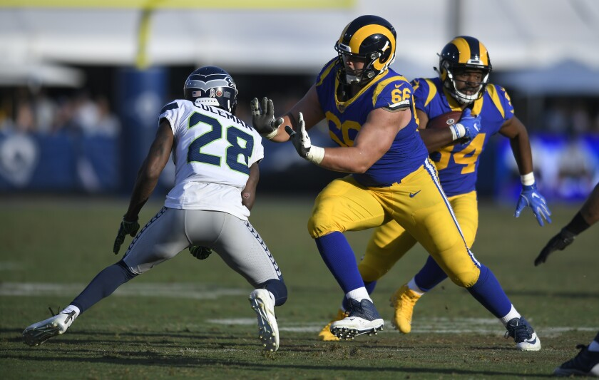 Rams offensive lineman Austin Blythe (66) blocks Seattle's Justin Coleman to allow Malcolm Brown (34) room to run Nov. 11, 2018, at the Coliseum.