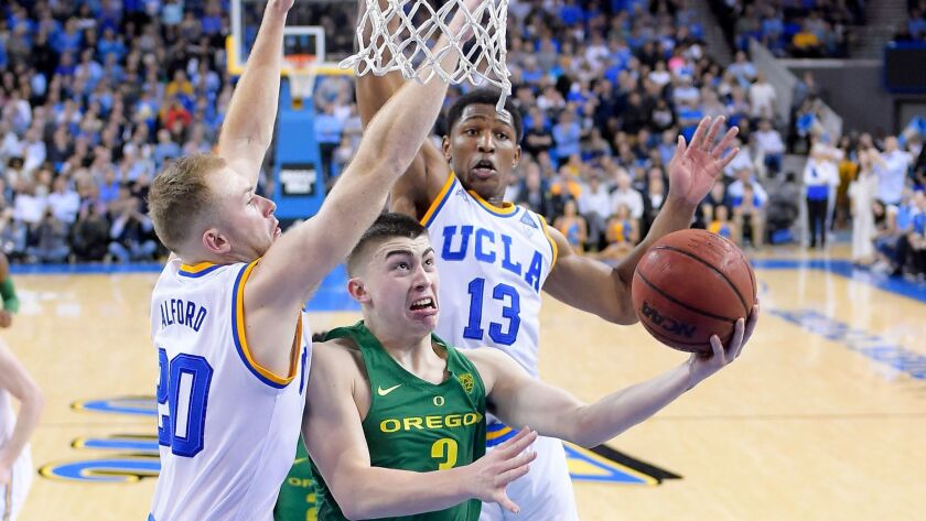 UCLA guard Bryce Alford, left, and forward Ike Anigbogu defend against Oregon's Payton Pritchard on Feb. 9.