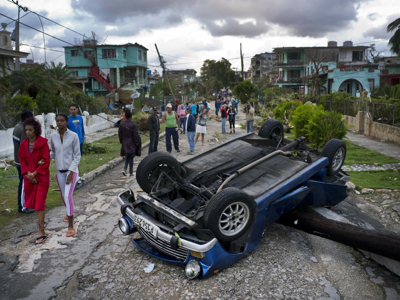 A car overturned by a tornado lies atop a utility pole in Havana. A tornado and pounding rains smashed into the eastern part of Cuba's capital overnight.