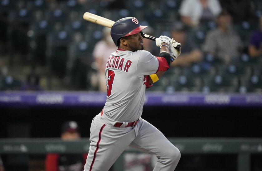 Washington Nationals' Alcides Escobar follows the flight of his double off Colorado Rockies starting pitcher Kyle Freeland in the first inning of a baseball game Tuesday, Sept. 28, 2021, in Denver. (AP Photo/David Zalubowski)