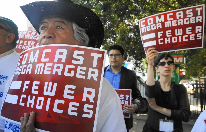Protesters rally outside the state building in downtown Los Angeles ahead of a California Public Utilities Commission hearing on the proposed Comcast-Time Warner Cable merger.