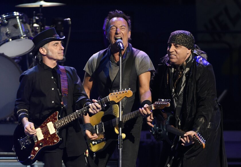 "FILE - In this Tuesday, March 15, 2016 file photo, Bruce Springsteen, center, performs with Nils Lofgren, left, and Steven Van Zandt of the E Street Band during their concert at the Los Angeles Sports Arena in Los Angeles. Fourth-grader Xabi Glovsky and his father, Scott, attended the sold-out show, and they caught Springsteen's eye with a homemade sign that said: ""Bruce, I will be late to school tomorrow. Please sign my note."" After the show, Springsteen invited the pair backstage and he scribbled a note for the Claremont boy's teacher. The note said: ""Dear Ms. Jackson, Xabi has been out very late rocking & rolling. Please excuse him if he is tardy."" (Photo by Chris Pizzello/Invision/AP)"