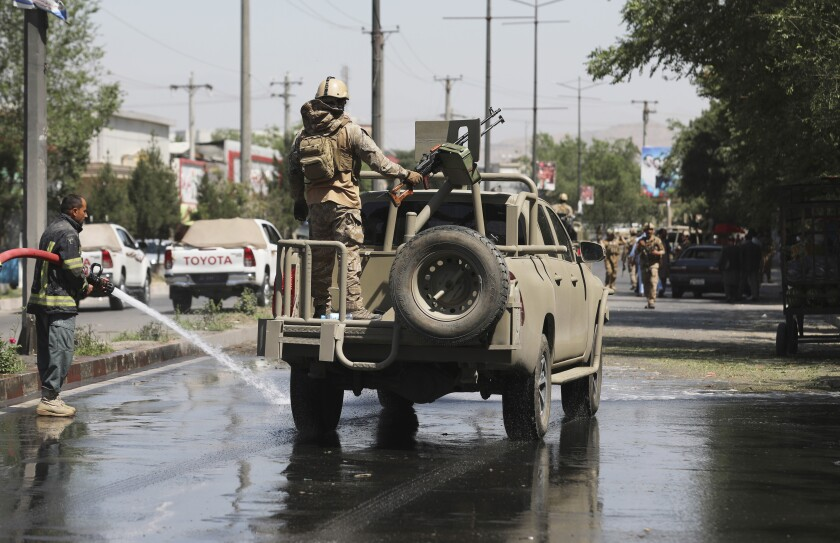 Afghan security personnel leave the scene of a roadside bomb explosion in Kabul, Afghanistan