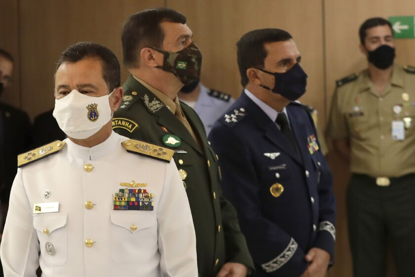 Brazil's new military commanders, Navy commander Admiral Almir Garnier, left, Army commander General Paulo Sergio, center, and Air Force commander Brigadier Carlos de Almeida Baptista Jr., right, stand during their presentation ceremony at the Ministry of Defense headquarters in Brasilia, Brazil, Wednesday, March 31, 2021. The new leaders of all three branches of Brazil's armed forces were named after the previous ones jointly resigned following President Jair Bolsonaro's replacement of the defense minister, causing widespread apprehension of a military shakeup to serve the president's political interests. (AP Photo/Eraldo Peres)