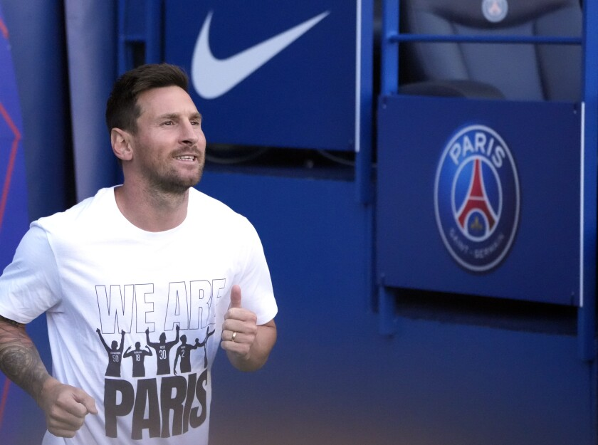 PSG's Lionel Messi runs onto the pitch in front of fans for the first time