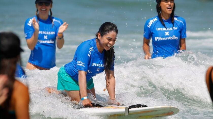 Margarita Molina-Corona, 25, of Linda Vista surfs a wave at the They Will Surf Again event put on by