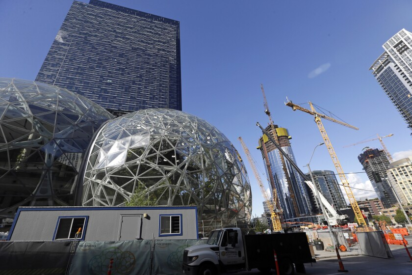 In this Wednesday, Oct. 11, 2017, photo, large spheres take shape in front of an existing Amazon bui