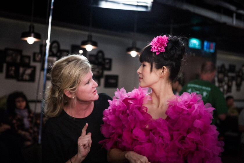 """Director Dennie Gordon talks with Ziyi Zhang on the set of the movie """"My Lucky Star."""""""