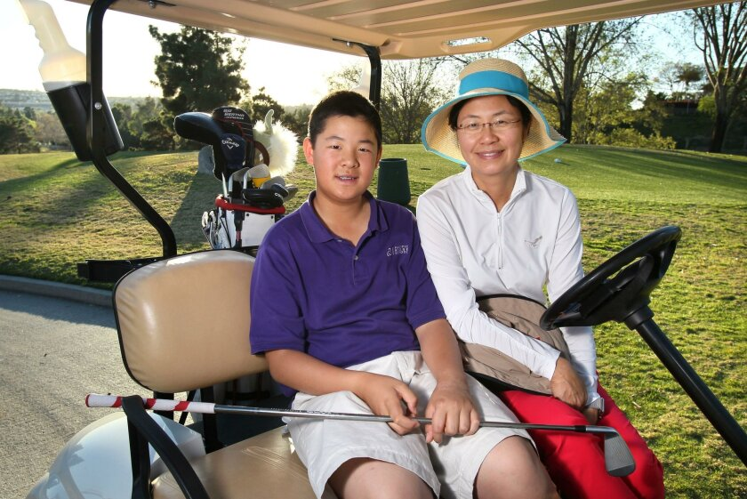 Alexander Yang, 13, with his mom Nancy Wong along hole 11 at the Shadowridge Country Club in Vista. Wong gave up her career in international banking to help her son pursue his dream of a PGA career.