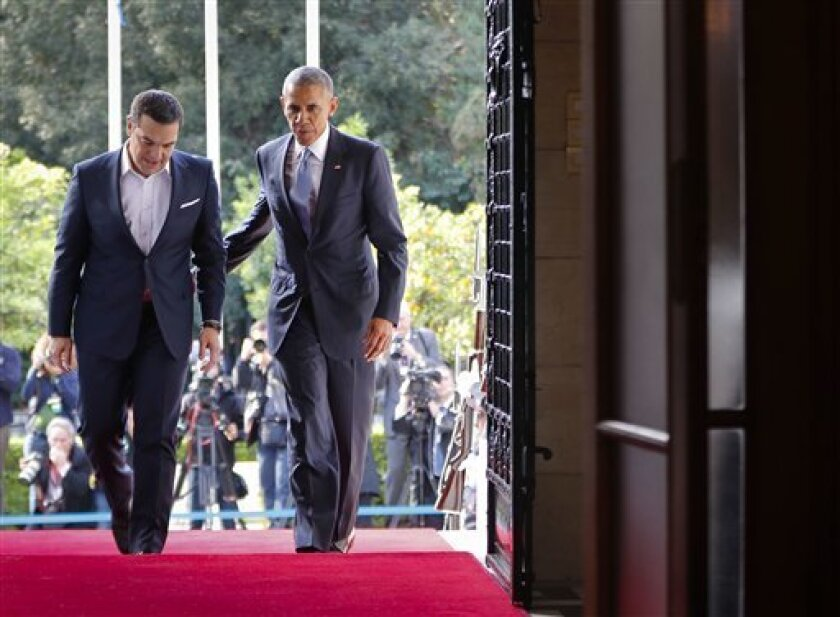 El presidente de EEUU, Barack Obama, camina hacia el palacio Maximos con el primer ministro griego, Alexis Tsipras, para comenzar su reunión conjunta y rueda de prensa en Atenas, el martes 15 de noviembre de 2016.
