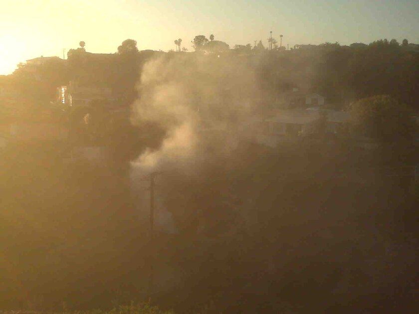 Smoke billows from a small fire on Avenida Amantea. Photo: Melissa Macis