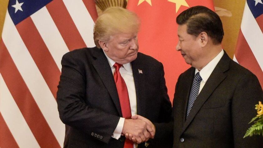 President Donald Trump shakes hands with China's President Xi Jinping at the end of a press conference in Beijing.