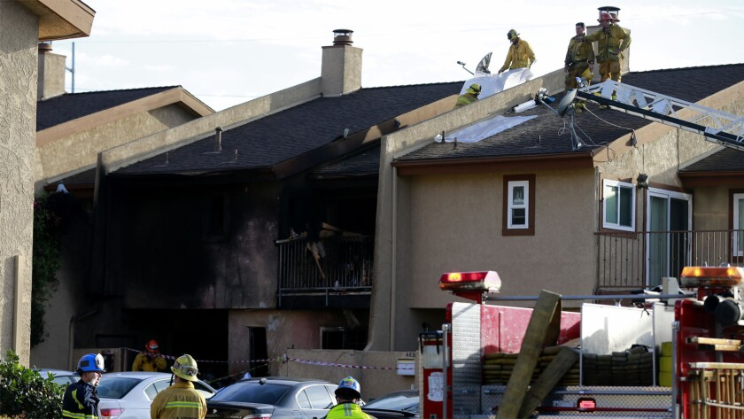 Firefighters work on the roof of a residence after the Hawthorne crash.
