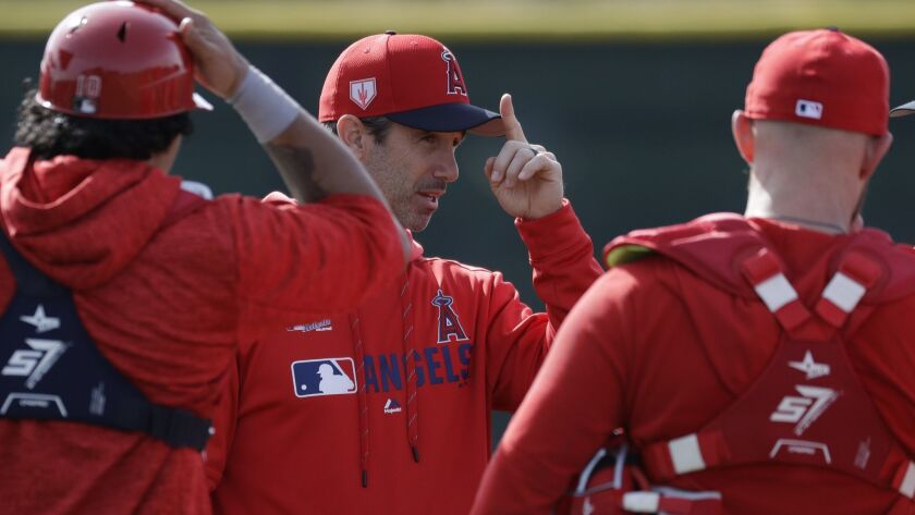 Los Angeles Angels manager Brad Ausmus talks with catchers during practice at their spring baseball