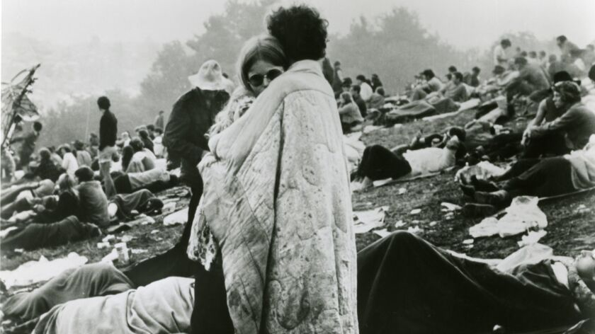 """A couple huddles at the fabled 1969 Woodstock music festival in Bethel, New York, where nearly half a million young people gathered for what was billed as """"three days of peace & music."""""""