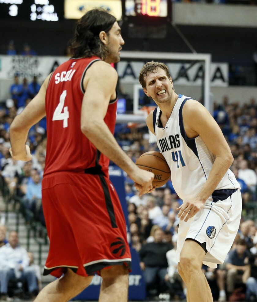 Toronto Raptors' Luis Scola (4) of Argentina watches as Dallas Mavericks' Dirk Nowitzki (41) of Germany argues for a foul call against the Raptors during the second half of an NBA basketball game Tuesday, Nov. 3, 2015, in Dallas. The Raptors won 102-91. (AP Photo/Tony Gutierrez)