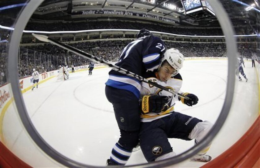 Winnipeg Jets' Eric Tangradi (27) collides with Buffalo Sabres' Brian Flynn (65) during the second period of their NHL hockey game in Winnipeg, Manitoba, Tuesday, April 9, 2013. (AP Photo/The Canadian Press, Trevor Hagan)