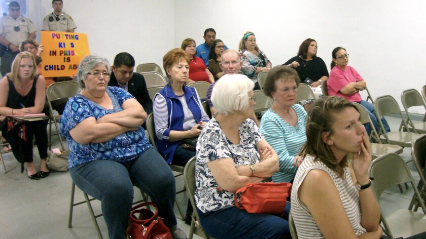Residents of Jim Wells County listen to comments during a public meeting about a proposal to turn an abandoned nursing home into a family immigrant detention center.