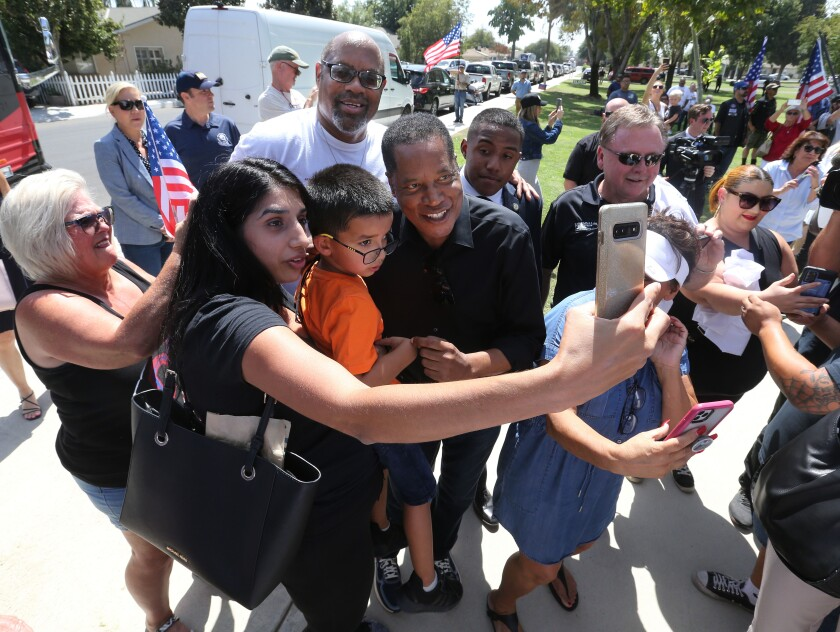 A woman and her 5-year-old son take a photograph with gubernatorial candidate Larry Elder in Bakersfield.