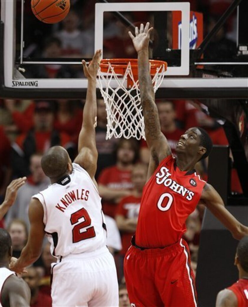 St. John's Dwayne Polee Jr. goes up to try to block a shot by Louisville's Preston Knowles during the first half of their NCAA college basketball game in Louisville, Ky., Wednesday, Jan. 19, 2011.  (AP Photo/Ed Reinke)