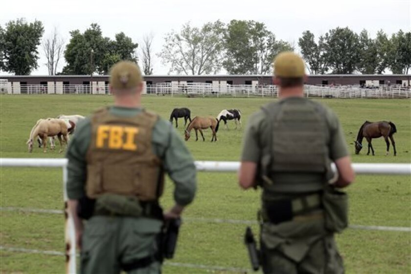 FILE - In this June 12, 2012 file photo, FBI agents overlook a horse ranch under investigation in Lexington, Okla. A federal judge in Texas sentenced Jose Trevino Morales, the brother of two Mexican cartel leaders to 20 years in prison on Thursday, Sept. 5, 2013, for running a money laundering operation from a sprawling horse ranch in Oklahoma. Sentencing is also expected for Francisco Antonio Colorado Cessa, Fernando Solis Garcia, Eusevio Maldonado and Raul Ramirez, who pleaded guilty in April