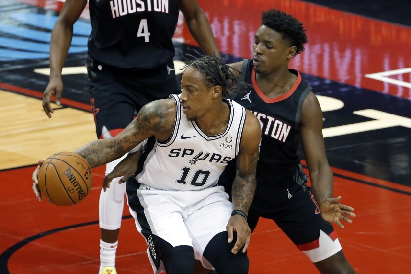 San Antonio Spurs forward DeMar DeRozan (10) drives to the basket in front of Houston Rockets forward Jae'Sean Tate, right, during the first half of an NBA basketball game Saturday, Feb. 6, 2021, in Houston. (AP Photo/Michael Wyke)