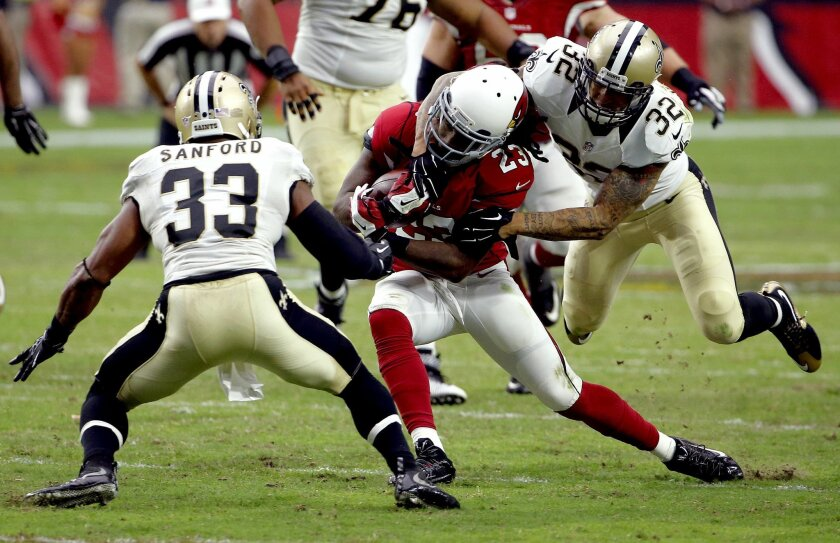 Arizona Cardinals running back Chris Johnson (23) his hit by New Orleans Saints strong safety Kenny Vaccaro (32) as strong safety Jamarca Sanford (33) defends during the second half of an NFL football game, Sunday, Sept. 13, 2015, in Glendale, Ariz. (AP Photo/Ross D. Franklin)