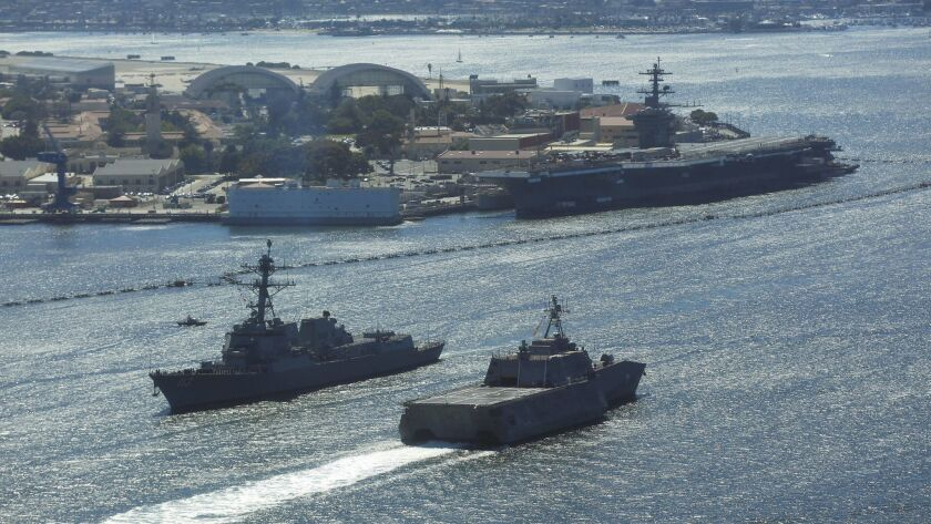The Arleigh Burke-class destroyer John Finn, left, and the littoral combat ship Montgomery pass each other in San Diego Bay as the aircraft carrier Theodore Roosevelt is docked at Naval Base Coronado on June 26, 2018.