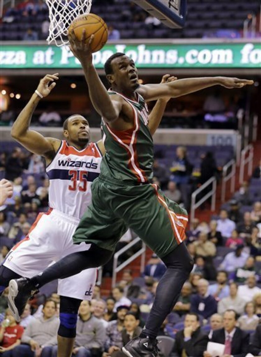 Milwaukee Bucks center Samuel Dalembert (21), of Haiti, shoots pastth Washington Wizards forward Trevor Booker (35) in the first half of an NBA basketball game, Wednesday, March 13, 2013, in Washington. (AP Photo/Alex Brandon)