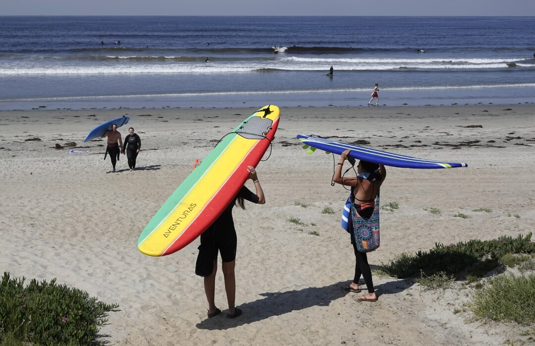 Andrea Lizardi, left, and Angeli Ruvalcaba walk to surf in Pacific Beach after local beaches reopened to activities such as walking, running, and surfing on April 27, 2020. Beaches have been closed for several weeks due to the coronavirus.