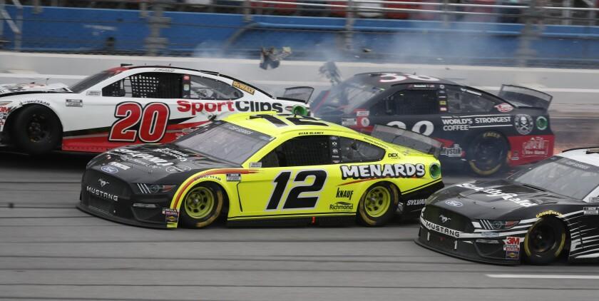 Ryan Blaney approaches the finish line as Erik Jones crashes at the at Talladega Superspeedway in Talladega Ala. on Monday.