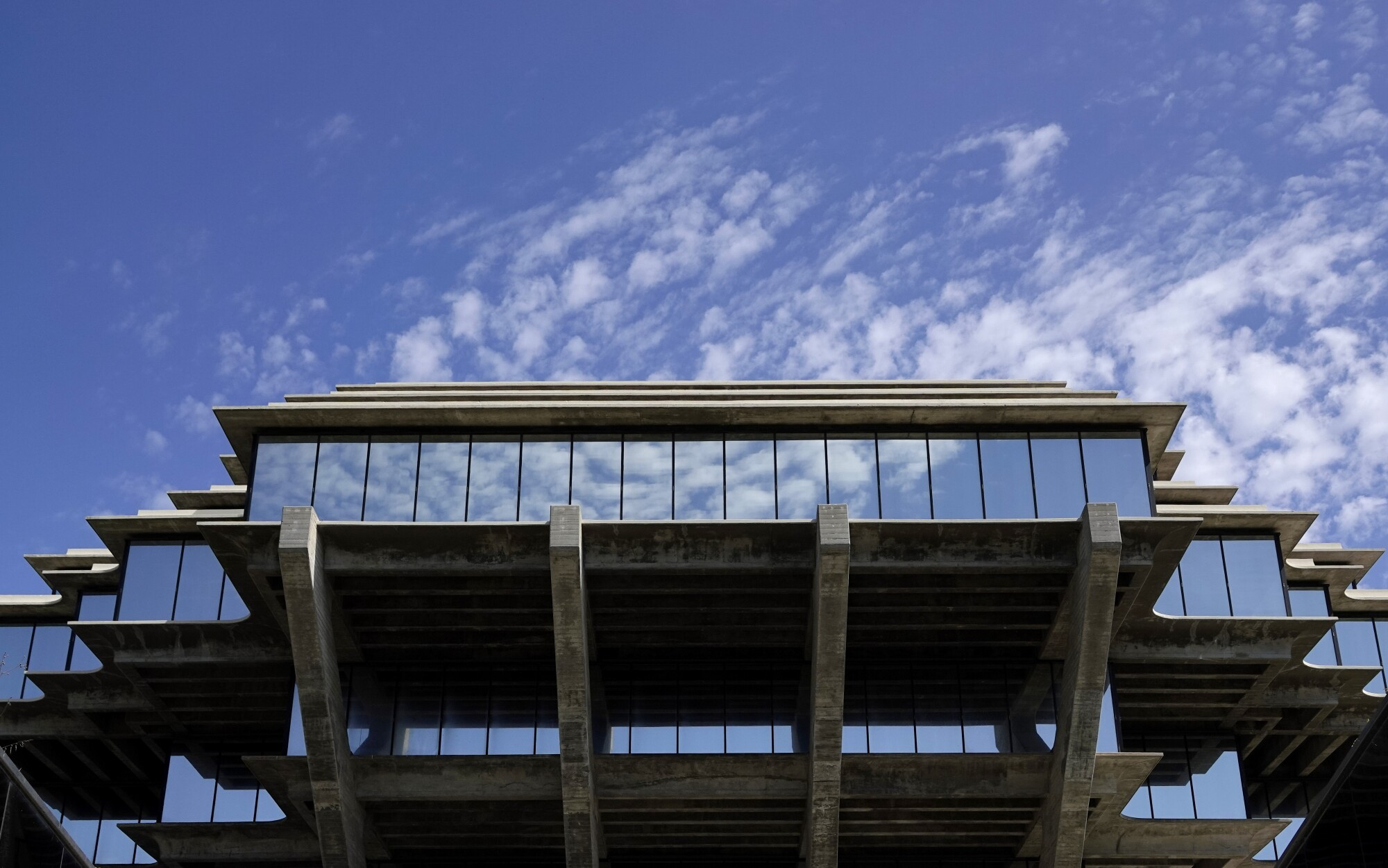 Clouds are reflected in the Geisel Library windows at UC San Diego in August.