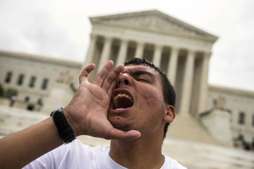 Gerson Quinteron of Washington, yells during a demonstration on immigration at the Supreme Court in Washington, Thursday, June 23, 2016. A tie vote by the Supreme Court is blocking President Barack Obama's immigration plan that sought to shield millions living in the U.S. illegally from deportation