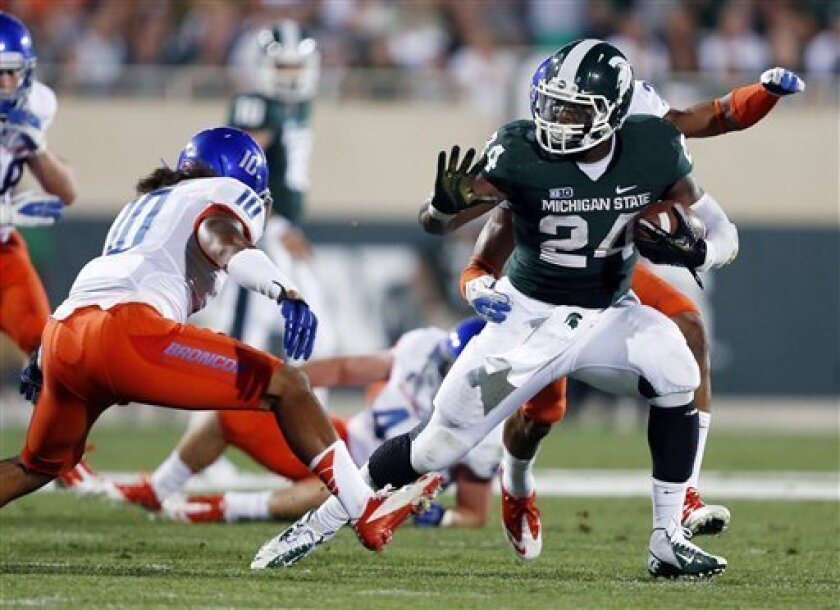 Michigan State's Le'Veon Bell, right, rushes against Boise State's Jeremy Ioane (10) during the first quarter of an NCAA college football game, Friday, Aug. 31, 2012, in East Lansing, Mich. (AP Photo/Al Goldis)