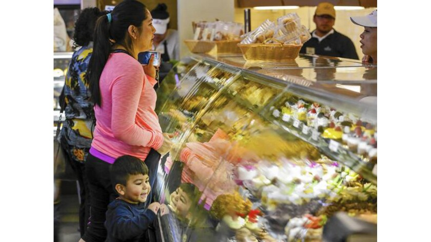 A little boy admires the colorful pastries as his mother places an order at Porto's Bakery & Cafe in Glendale. The bakery has thrived for four decades, fending off national chains, recessions and low-carb fads along the way.