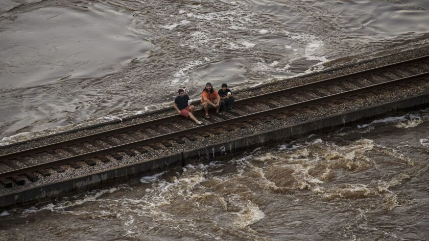 People sit on a railroad track near Lumberton, Texas, as floodwaters rush beneath them.