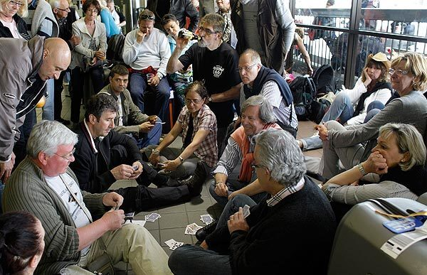 Stranded French tourists play cards and wait on the floor near the Air France ticket counter at LAX in hopes of getting on one of the four Air France flights departing for Paris on Tuesday.