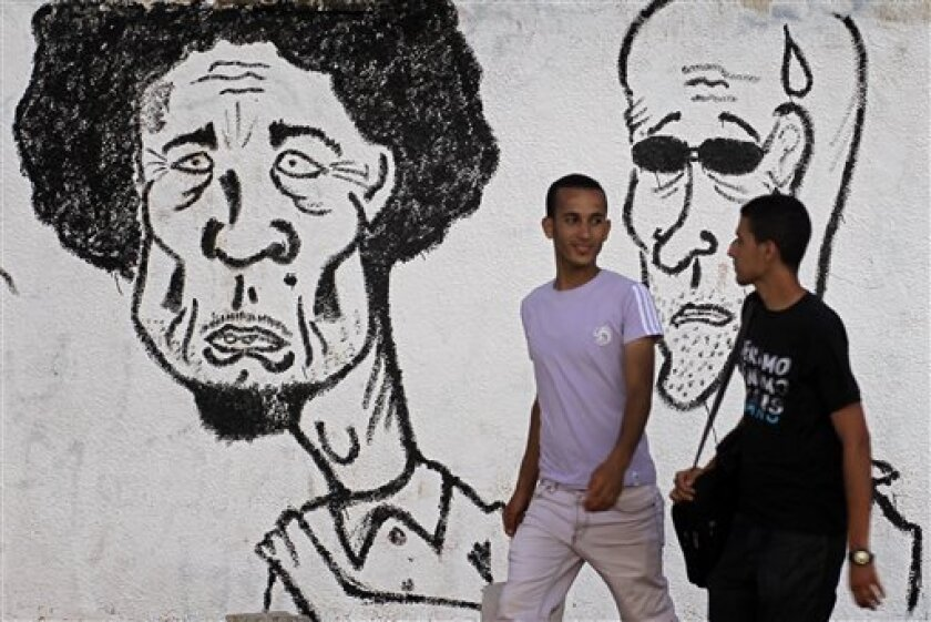 Libyans walk past graffiti depicting Libyan dictator Moammar Gadhafi in the rebel-held Benghazi, Libya,  Monday, July 4, 2011. A senior Libyan official said Monday that progress has been made in talks with rebels on ending more than four months of fighting, but a top rebel leader denied that any ne