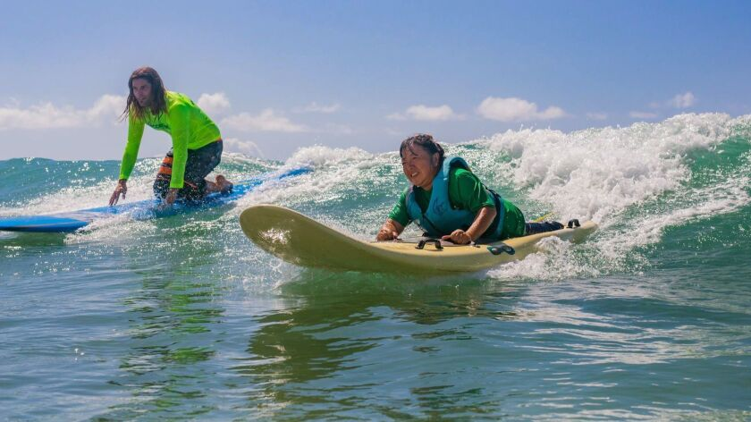 OAHU, HAWAII - Kuwana and an AccessSurf volunteer riding a wave at White Plains Beach. On Oahu, peop