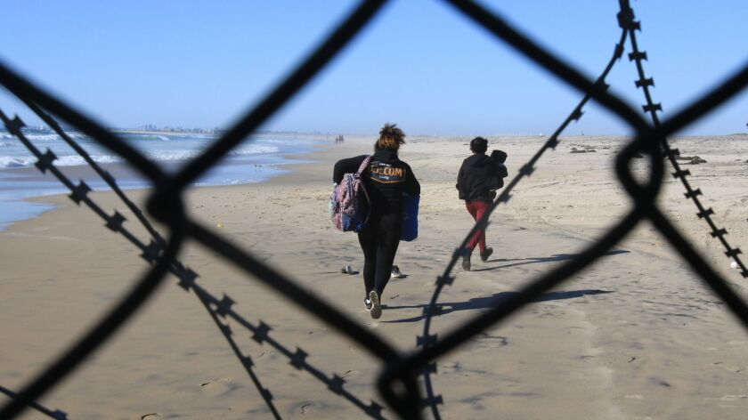 Two women, one carrying a young child, followed a group of roughly 20-30 migrants who squeezed throu