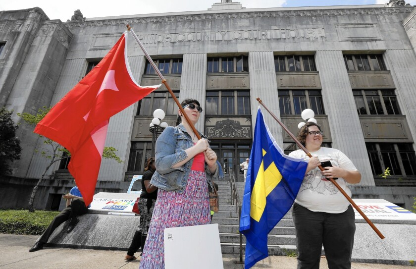 Engaged couple Karen Welch, left, and Brittany Raymond, both of Brandon, Miss., wave equality flags outside the Hinds County Courthouse in Jackson, Miss., on June 26 after Mississippi Atty. Gen. Jim Hood ordered court clerks not to issue marriage licenses to same-sex couples.