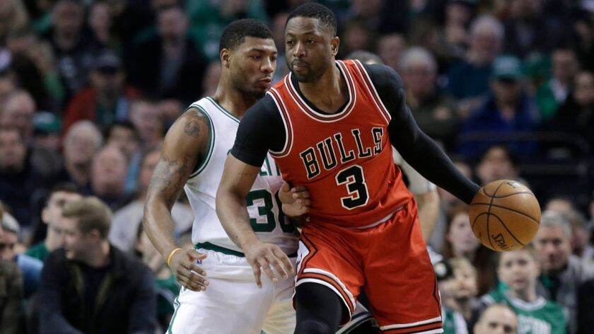 Boston Celtics guard Marcus Smart, left, tries to block Chicago Bulls guard Dwyane Wade, right, in t