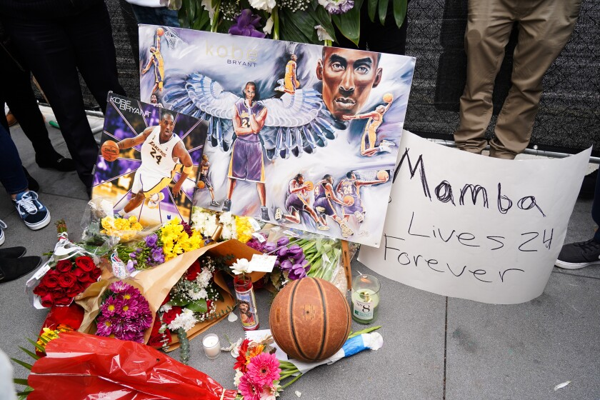 Flowers and tributes are left at a makeshift memorial for Kobe Bryant outside Staples Center on Sunday.